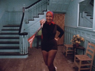 "The always head-scarved, apparently patriotic Little Edie waves a flag and dances in ""Grey Gardens."""
