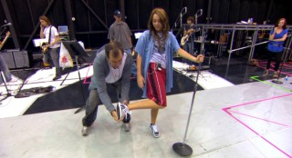 """High School Musical"" director Kenny Ortega schools Miley Cyrus on how to look cool and spontaneous while kicking a microphone stand back up into place."