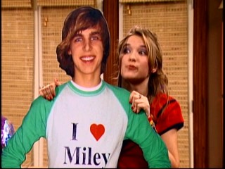 "Lilly (Emily Osment) votes that Miley give Jake Ryan (Cody Linley), the apologetic movie star of this cardboard standee, another chance in ""Achy Jakey Heart."""