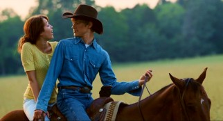 On a horse, Miley gets up close and personal with childhood friend turned cowboy Travis Brody (Lucas Till).