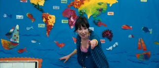 Standing in front of a colorful world map, elementary school teacher Poppy Cross (Sally Hawkins) looks pleased by her student's answer.