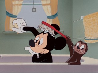 "A baby seal lends bathing Mickey a helping hand (and head scrub brushing) in ""Mickey and the Seal."""