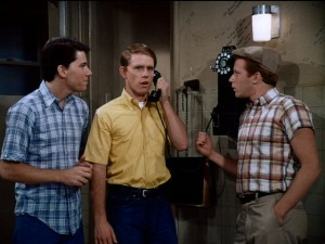 With support from Potsie (Anson Williams, left) and Ralph Malph (Donny Most, right), Richie Cunningham (Ron Howard, center) puts on an adult voice to inquire about vacation property.