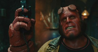 Hellboy (Ron Perlman) approaches danger with the help of a gun and some smug confidence.