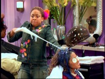 "Raven struggles to remove a rubber glove that has fused itself to Alana's painted hair via chewing gum in ""Run Raven Run."""