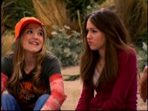 Lilly (Emily Osment) fawns over Jake while Miley (Miley Cyrus) looks in disgust.