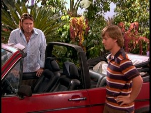 "Robbie and son Jackson (the deceptively young Jason Earles) examine the boy's newly-purchased ""girl car."""