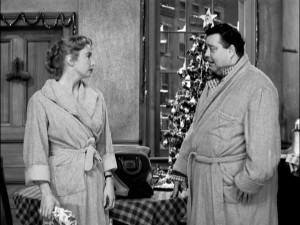 """Honeymooners"" Alice (Audrey Meadows) and Ralph Kramden (Jackie Gleason) exchange gifts in front of their start-topped tree."