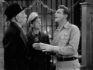 Sheriff Andy Taylor (Andy Griffith) is tested by miserly storeowner Ben Weaver (Will Wright), while Barney Fife (Don Knotts) looks on.
