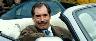 One-time Bond Timothy Dalton provides a winning mix of suave and smarm as grocery store manager/obvious villain Simon Skinner.