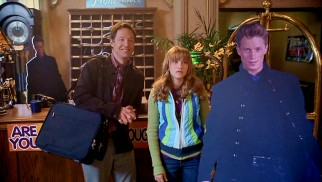 Three's company. Neal (George Newbern) and Melissa (Emily Osment) are joined by a cardboard Tripp Zoome standee (Jonathan Keltz) while checking in at the Merc Hotel.