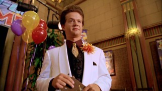 32-year-old Jason Earles rocks a white jacket, a lapel flower, and one wicked dope pompadour as hotelier Merv Kilbo.