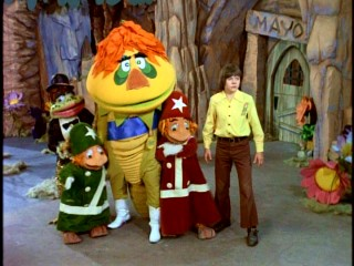Jimmy and some of his Living Island friends (Judy Frog, Cling, Clang, and H.R. Pufnstuf) are taken aback by the sight of Witchiepoo jumping out of a large cake.