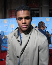 "Chris Warren Jr. (Zeke in ""High School Musical"" 1 and 2) looks serious in a trench coat on the sequel's red carpet DVD event."