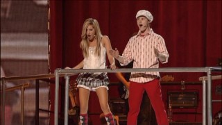 Scantily clad and sexually charged (respectively), Ashley Tisdale and Lucas Grabeel overlook the crowded stage.
