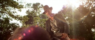 A bold and deliberate lens flare serves to emphasize the heroism already present in this low-angle shot of Indy on an elephant.