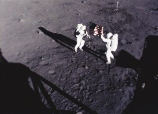 Neil Armstrong and Buzz Aldrin affix the United States flag to the lunar surface on Apollo 11.