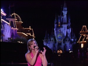 Ann Cochran wears pink and is complemented by the sight of Cinderella's Castle in back
