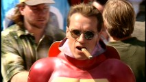 "Making a movie in a heavy costume would make some ask for water or a fan, but not Arnold Schwarzenegger. He smokes a cigar on a break from filming, as seen in ""The Making of a Hero."""