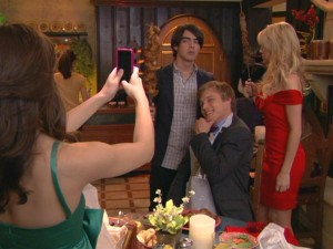 Joe (Joe Jonas) and Stella (Chelsea Staub) attempt to skewer each other at dinner, but not before Macy has them freeze with Van Dyke (Chuck Hittinger) for a photo op.
