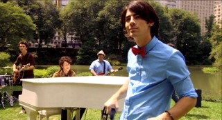 "Joe Jonas rocks out with tambourine and red bow tie in the Brothers' Central Park music video ""Love Is On Its Way."""