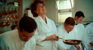 Towering over her male classmates, Julia Child (Meryl Streep) tilts back to celebrate her successful omelet flip in culinary class.