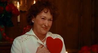 At a Valentine's Day dinner, smiling Julia Child (Meryl Streep) places her hand between her real and decorative hearts.