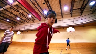 Just a normal teenaged boy offstage, Justin Bieber shows off his basketball skills for the camera in a casual gym visit with both of his Stratford, Ontario friends.