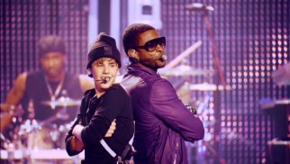 "Their awkward first meeting long behind them, Justin Bieber and Usher finish their song ""Somebody to Love"" back-to-back to see who's taller. (Usher is.)"