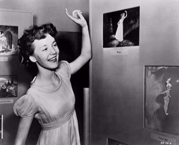 "Kathryn Beaumont poses alongside a picture of Wendy. Beaumont served as the voice and live-action reference model for the eldest Darling child in Disney's 1953 animated classic ""Peter Pan."""