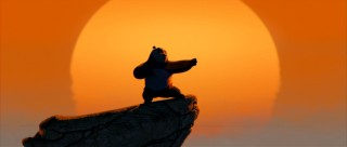 Atop a cliff against an orange sunset sky, Po strikes an iconic kung fu panda pose.