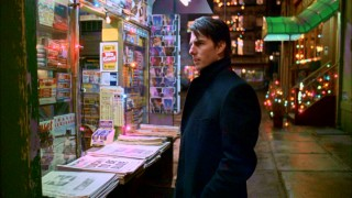 William Harford (Tom Cruise) looks perturbed while buying a newspaper from a vendor on a fake New York City street. Is it his troubling screencap neighbor or the creepy guy that's following him?