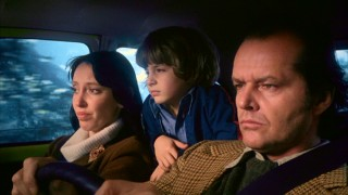 The Torrance family -- Wendy (Shelley Duvall), Danny (Danny Lloyd), and Jack (Jack Nicholson) -- drive to snowy Colorado, where they will spend the winter.