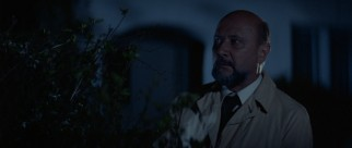 Dr. Sam Loomis (Donald Pleasence) waits in the bushes near Michael Myers' old home.
