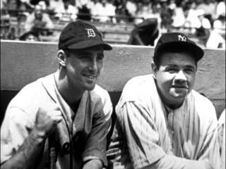 Hank Greenberg and some other baseball player share a moment together in a dugout.