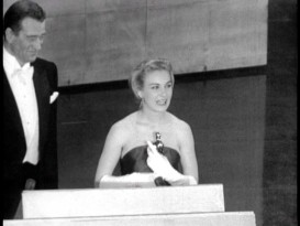 A happy John Wayne looks on as Joanne Woodward accepts the Academy Award for Best Lead Actress in a Fox Movietone newsreel clip.