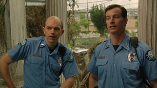Officers Huebel (Paul Scheer) and Sheer (Rob Huebel) investigate the Watsons with heavy suspicion.