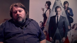 "Director Ben Wheatley discusses bringing Ballard to the big screen in front of a ""High-Rise"" poster."