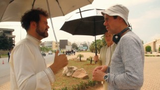 "Tom Tykwer directs an umbrella-carrying Alexander Black on the desert set of ""A Hologram for the King."""