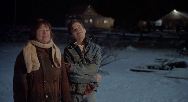 "Mother (Kathy Bates) and eldest son (Edward Furlong) admire a home of their own on a winter's night in ""A Home of Our Own."""