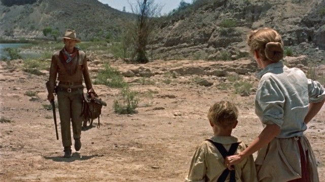 "In the New Mexican desert, a stranger (John Wayne) approaches the ranch of a mother and son at the start of ""Hondo."""