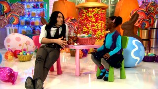 Russell Brand stretches his long legs during his colorful interviews with kids.