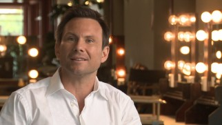 "Christian Slater discusses ""Choozy Doozy"", the top-rated game show of the future his character hosts in his uncredited cameo."