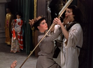 Sue Allen (Phyllis Kirk) is struck by the resemblance this wax Joan of Arc bears to her recently poisoned best friend.