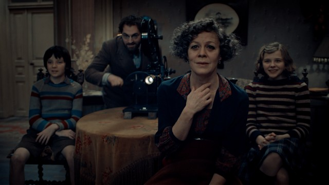 The power of cinema is unleashed as film author Rene Tabard (Michael Stuhlbarg) cranks a projector for Hugo, Isabelle, and Mama Jeanne Méliès (Helen McCrory).