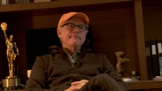 Director Barry Levinson sits casually in front of some awards in his featurette interview.