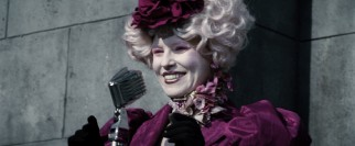 The interestingly-fashioned Effie Trinket (Elizabeth Banks) cheerily chooses the youths who will represent District 12 in the deadly 74th Annual Hunger Games.