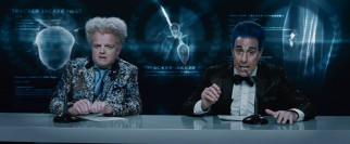 Claudius Templesmith (Toby Jones) and Caesar Flickerman (Stanley Tucci) provide Hunger Games color commentary in glitzy attire.
