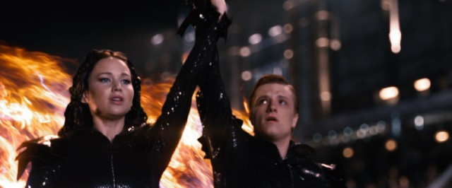District 12 tributes Katniss (Jennifer Lawrence) and Peeta (Josh Hutcherson) hold hands for all to see during their fiery Opening Ceremony appearance.