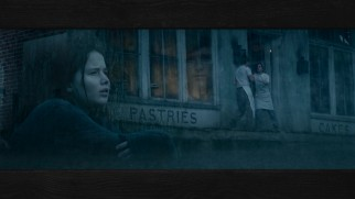 A cold, wet Katniss dreams of pastries while a ghostly Peeta looks on in Disc 2's menu montage.